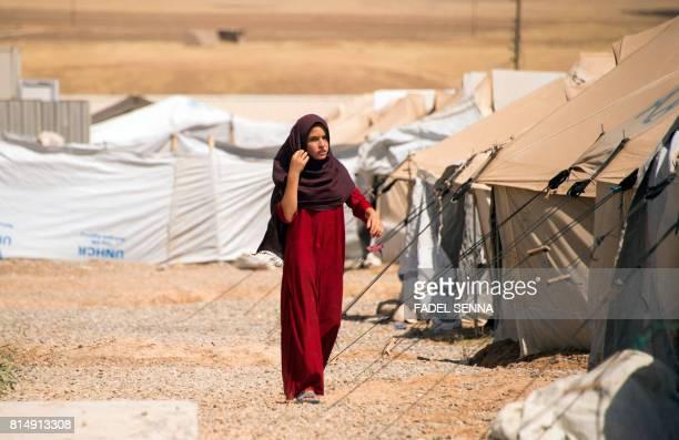A displaced Iraqi woman walks past tents at the Hasan Sham camp some 30 kilometres east of Mosul on July 15 2017 / AFP PHOTO / FADEL SENNA