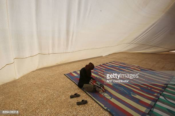 TOPSHOT A displaced Iraqi woman who fled the fight between Iraqi forces and the Islamic State group in Tal Afar sits inside a tent at the Badush camp...