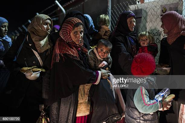 TOPSHOT Displaced Iraqi women and children from the embattled city of Mosul arrive on December 16 at the Sewdinan camp for internally displaced...