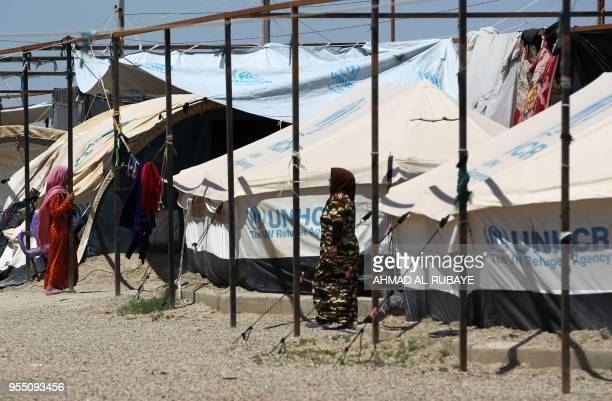 Displaced Iraqi women walk in a camp for internally displaced people near alKhalidiyeh in Iraq's western Anbar province on April 24 2018 While the...