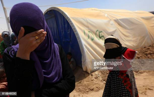 Displaced Iraqi women whose family members are accused of being Islamic State militants stand at the Jadaah camp on the outskirts of AlQayyarah south...
