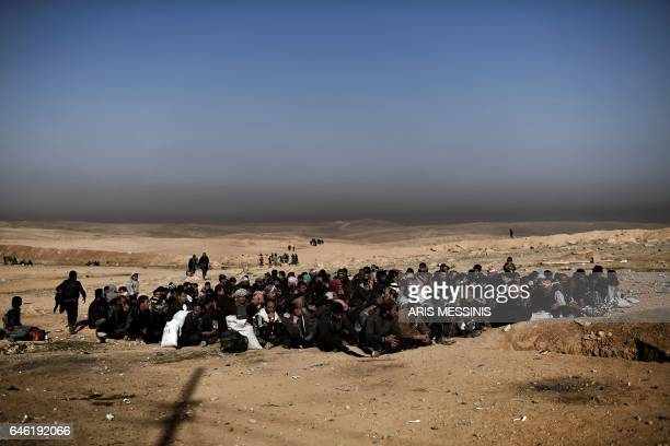 TOPSHOT Displaced Iraqis are seen gathered as they flee the city of Mosul while Iraqi forces battle against Islamic State group jihadists to...