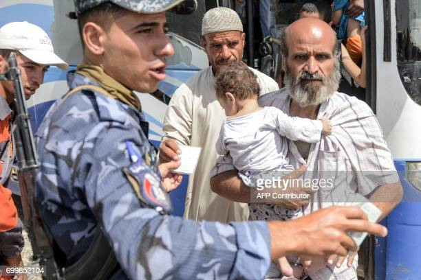 Displaced Iraqis arrive at the Hammam alAlil camp for internally displaced people south of Mosul on June 22 during the ongoing offensive by Iraqi...