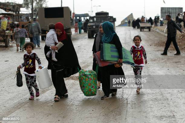 Displaced Iraqis carry their belongings as they flee their homes in an area west of Mosul on April 14 during the ongoing offensive to retake the city...