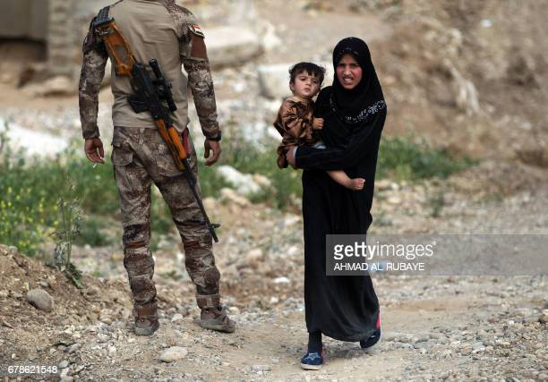 TOPSHOT Displaced Iraqis carry their belongings as they flee their homes in the northwestern Mosul neighbourhood of Musharifah on May 4 during an...