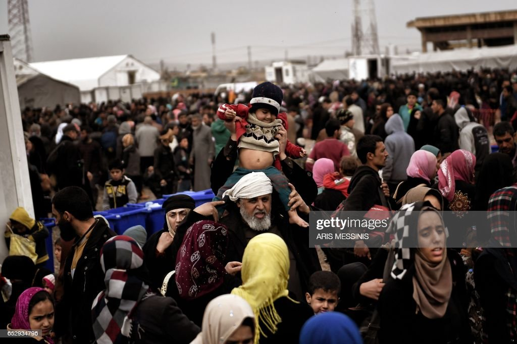 TOPSHOT - Displaced Iraqis from Mosul arrive at the Hamam al-Alil camp on March 13, 2017, during the government forces ongoing offensive to retake the western parts of the city from Islamic State (...