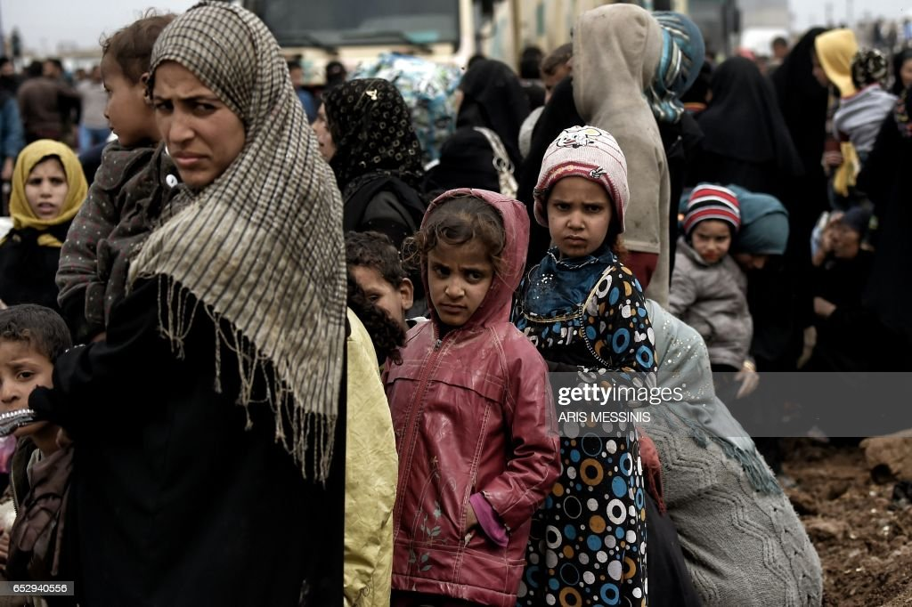 Displaced Iraqis from Mosul arrive at the Hamam al-Alil camp on March 13, 2017, during the government forces ongoing offensive to retake the western parts of the city from Islamic State (IS) group fighters. /