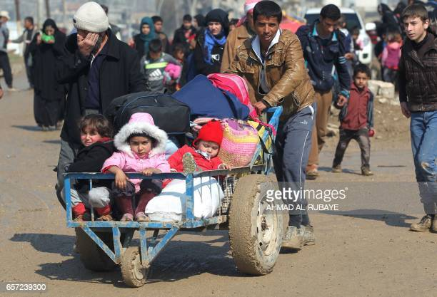 TOPSHOT Displaced Iraqis from Mosul walk towards refugee camps on March 24 after fleeing their city during the government forces ongoing offensive to...