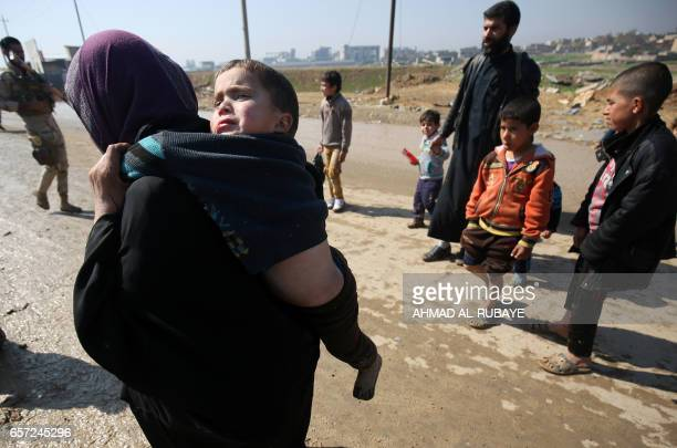 TOPSHOT Displaced Iraqis from Mosul walk towards the Hamam alAlil refugee camp on March 24 after fleeing their homes due to the government forces...