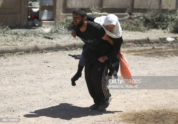 TOPSHOT Displaced Iraqis from Mosul's western Rabie neighbourhood flee their homes as security forces advance into the area during the ongoing...