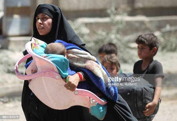 Displaced Iraqis from Mosul's western Rabie neighbourhood flee their homes as security forces advance into the area during the ongoing offensive...