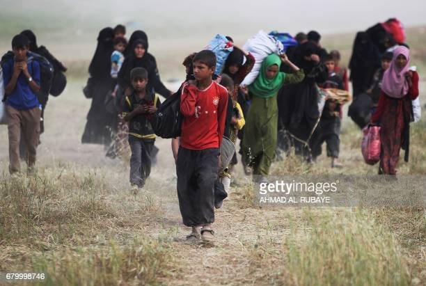 Displaced Iraqis from the Al-Haramat neighbourhood, north of Mosul, flee their homes on May 7 during the ongoing military offensive to retake the...