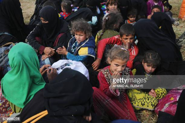Displaced Iraqis from the Al-Haramat neighbourhood, north of Mosul, gather on the side of the road as they flee their homes on May 7 during the...
