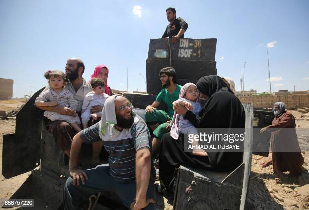 Displaced Iraqis from West Mosul's Al-Najjar neighbourhood sit on an army vehicle as they leave their homes on May 22 during the ongoing offensive by...