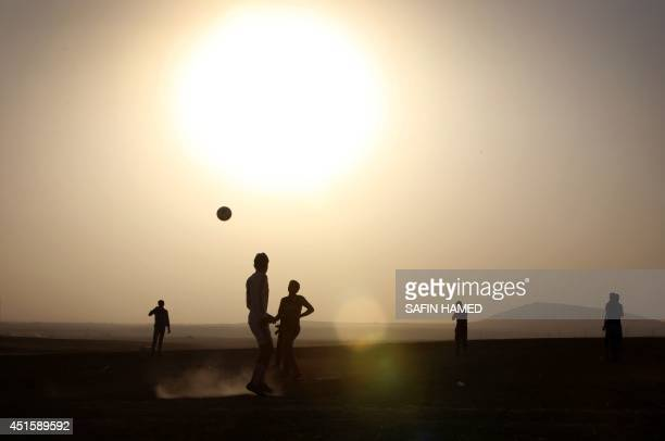 Displaced Iraqis play football at sunset at a temporary camp set up by the UN refugee agency to shelter people fleeing violence in northern Iraq on...