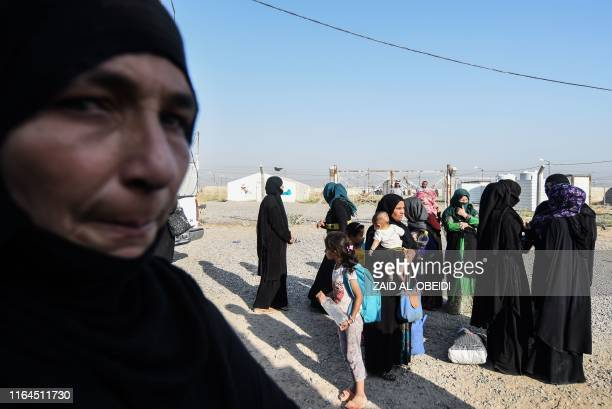 Displaced Iraqis prepare to board a bus at a camp for displaced people in Hammam al-Alil, south of the northern Iraqi city of Mosul, on August 27 as...
