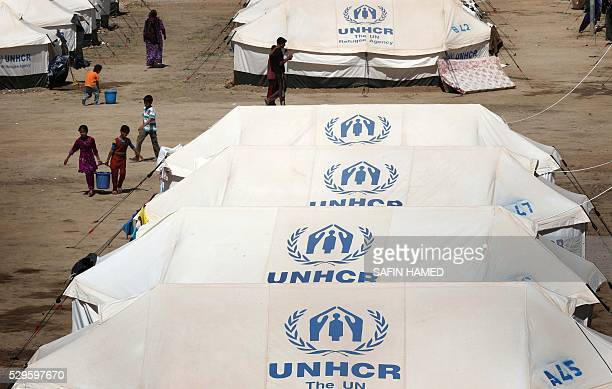 Displaced Iraqis stand outside their tents at a new camp set up to shelter civilians fleeing violence in the northern city of Mosul on May 9 2016 in...