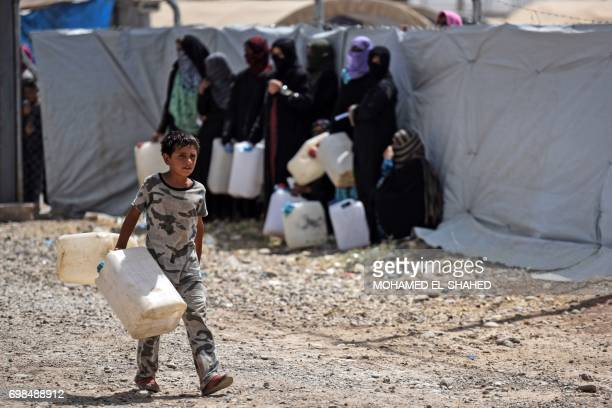 Displaced Iraqis wait to fill jerricans with water at alKhazir camp for the internally displaced located between Arbil and Mosul on June 20 during...