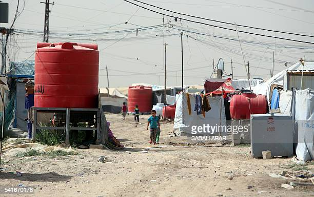 Displaced Iraqis walk at the Salam camp for people displaced from Ramadi and Tikrit on June 20 2016 on the outskirts of the capital Baghdad The...
