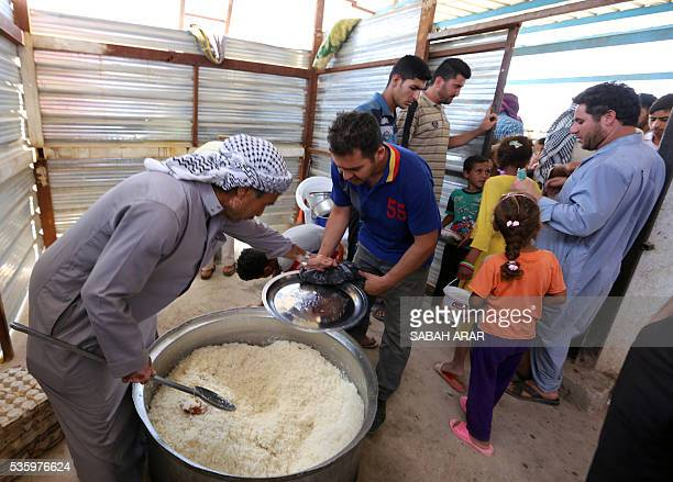 Displaced Iraqis who fled fighting between government forces and the Islamic State group in Anbar province line up to collect donated food at the...