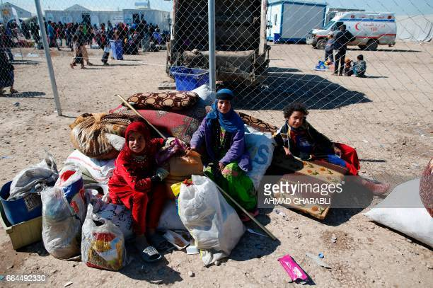 Displaced Iraqis who fled Mosul due to the ongoing fighting between government forces and Islamic State group jihadists sit with their belongings at...