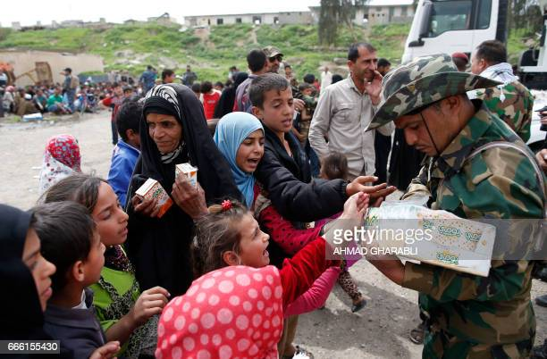 Displaced Iraqis who fled Mosul's Old City receive food as they arrive in the AlTayaran neighbourhood on April 8 during an offensive by government...