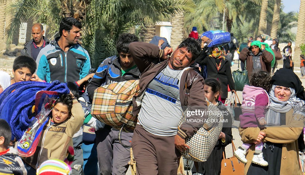 TOPSHOT - Displaced Iraqis, who fled regions controlled by the Islamic State (IS) group near Fallujah, carry their belongings on February 8, 2016 as they arrive in the Jwaibah area, on the eastern outskirts of Ramadi, after pro-government troops retook it from jihadists. / AFP / MOADH