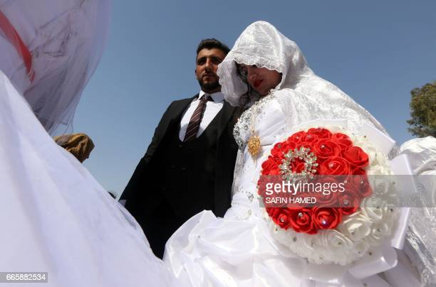 Displaced Iraqis who fled the fighting in the northern city of Mosul take part in a collective wedding ceremony funded by the Emirates Red Crescent...