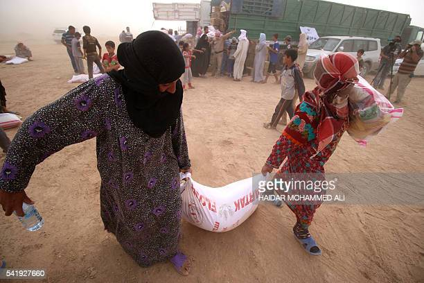 Displaced Iraqis who fled the government's operation against the Islamic State group in the city of Fallujah carry bags of food donated by a NGO...