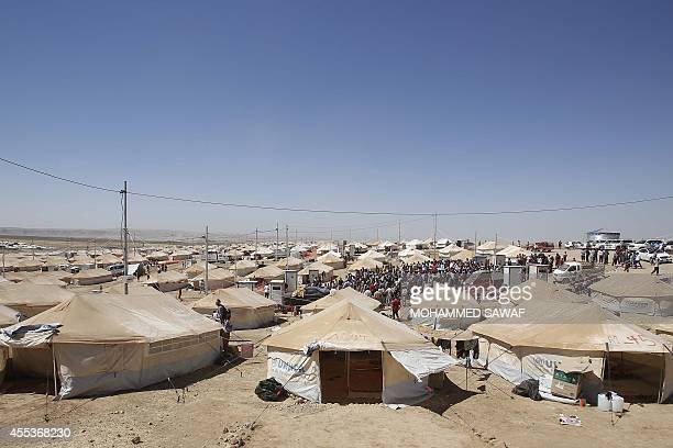 Displaced Iraqis who have fled the offensive led by the Islamic State jihadist group gather on September 13 2014 at a camp for displaced people in...