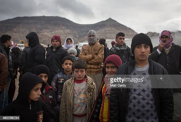 Displaced Iraqis, who were forced to flee their home because of Islamic State's advance earlier this year, queue for humanitarian aid that is being...