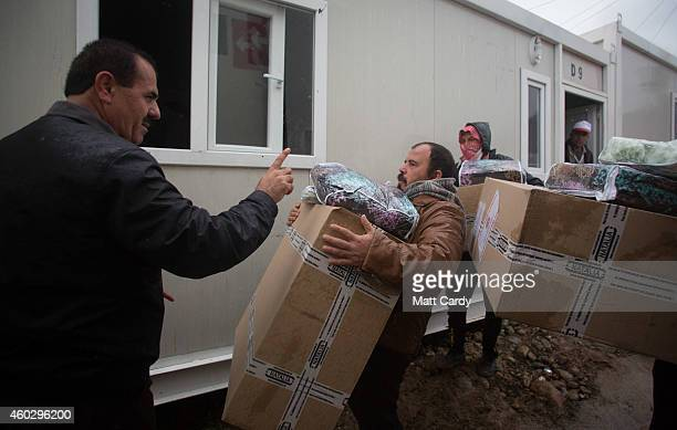 Displaced Iraqis, who were forced to flee their homes because of Islamic State's advance earlier this year, receive humanitarian aid that is being...