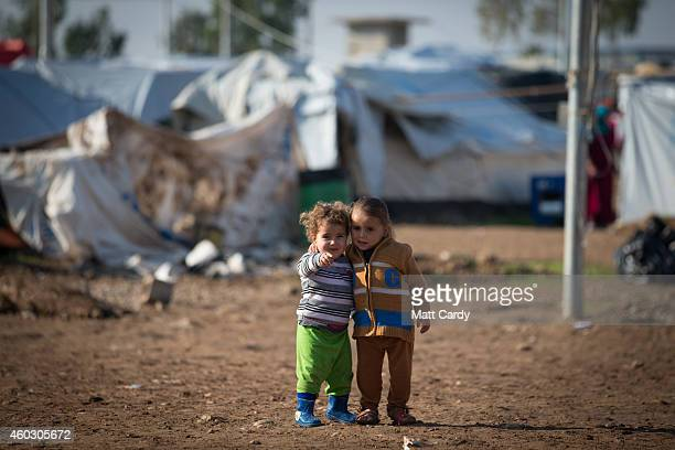 Displaced Iraqis who were forced to flee their homes because of Islamic State's advance earlier this year stand in front of tents that have been...