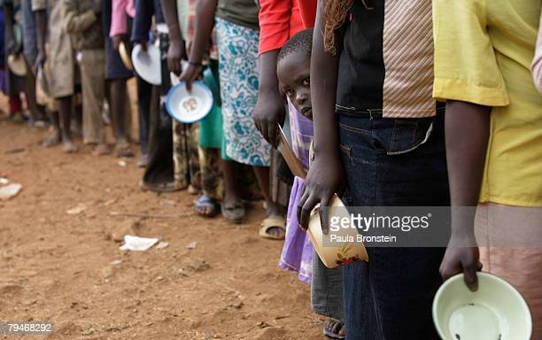 Displaced Kenyans wait for food at the Tigoni internally displaced persons camp on February 1 2008 in Tigoni Kenya Ethnic tribal conflicts sparked by...