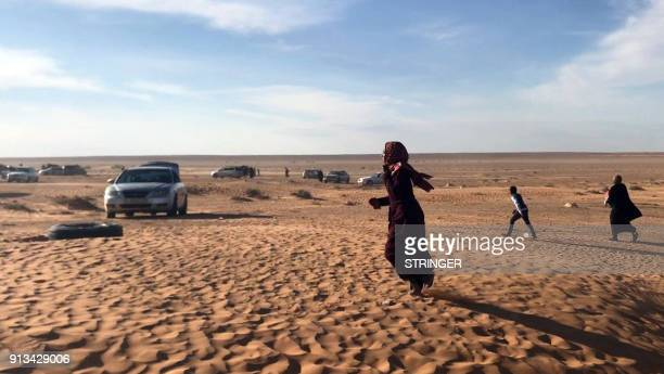 A displaced Libyan woman from the western city of Tawergha walks through the sand as cars are seen waiting to enter the city which lies about 250...