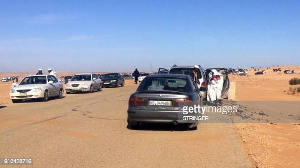 Displaced Libyans from the western city of Tawergha wait by their cars to enter the city which lies about 250 kilometres east of the capital Tripoli...