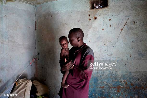 Displaced man holds his baby in the house where he is hosted after fleeing his village in central Mali, on September 30, 2019. - In central Mali, in...