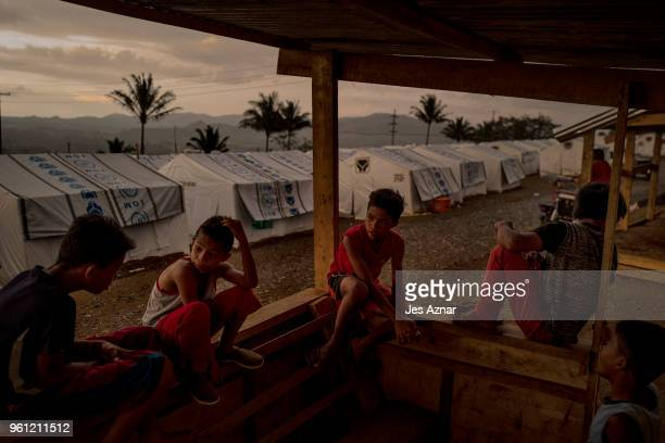 Displaced Marawi childrensitting under a shade inside a makeshift tent shelter area on May 14 2018 in Marawi Philippines With their homes destroyed...