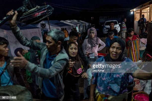 Displaced Marawi city residents gather their belongings from a truck as they arrive inside the Sarimanok tent city on May 16 2018 in Marawi...