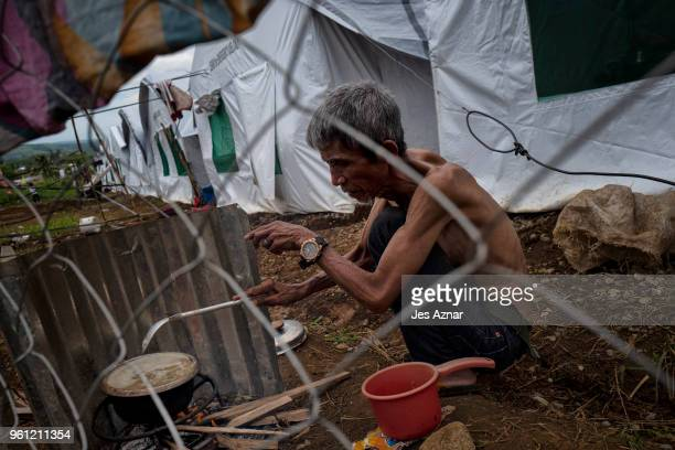 A displaced Marawi resident cook a meal in front of his shelter on the eve of Ramadan at the Sarimanok tent city on May 16 2018 in Marawi Philippines...