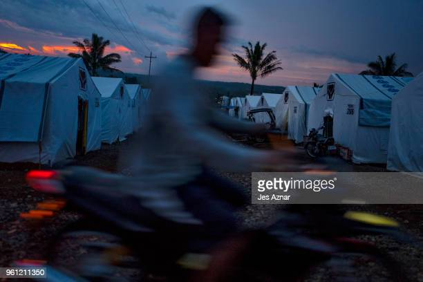 A displaced Marawi resident on motorcycle inside the Sarimanok tent city on the outskirt of Marawi on May 15 2018 in Marawi Philippines With their...