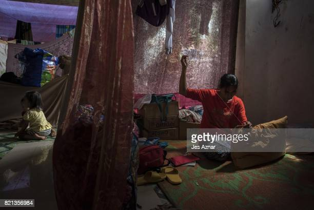 A displaced Marawi resident repairing a pillow inside a makeshift evacuation center on July 23 2017 in Saguiaran Lanao del Sur southern Philippines...