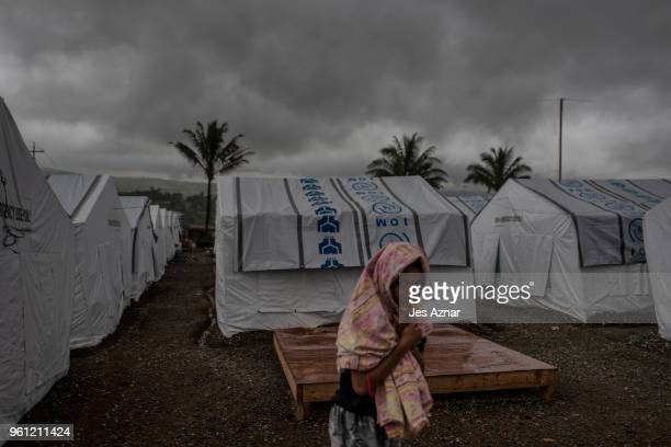A displaced Marawi resident walk past tent shelters inside the Sarimanok tent city on May 16 2018 in Marawi Philippines With their homes destroyed...