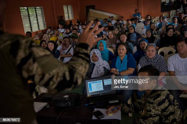 Displaced Marawi residents attend a meeting to discuss the cleanup of their communities with the military on October 19 2017 in Marawi southern...