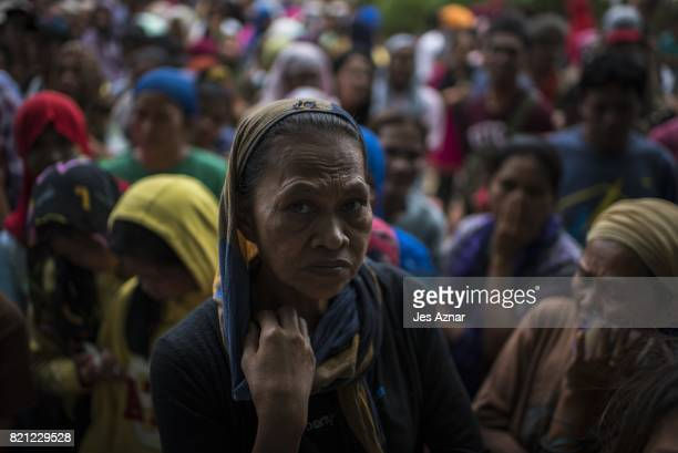 Displaced Marawi residents gather to receive food aid inside a makeshift evacuation center on July 23 2017 in Saguiaran Lanao del Sur southern...