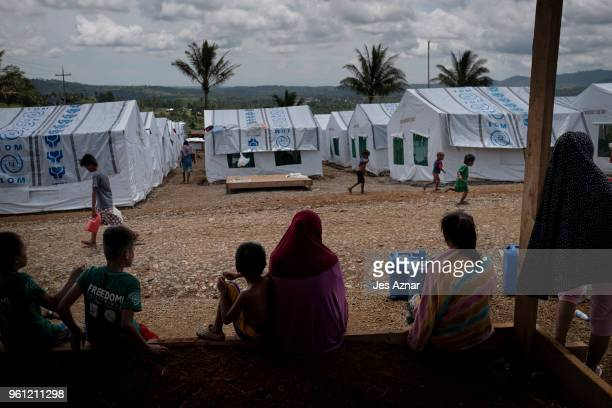 Displaced Marawi residents hudle under a shade inside a makeshift tent shelter area on May 14 2018 in Marawi Philippines With their homes destroyed...
