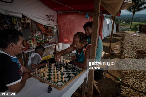 Displaced Marawi residents play chess to pass the time outside their tent shelter on May 14 2018 in Marawi Philippines With their homes destroyed and...