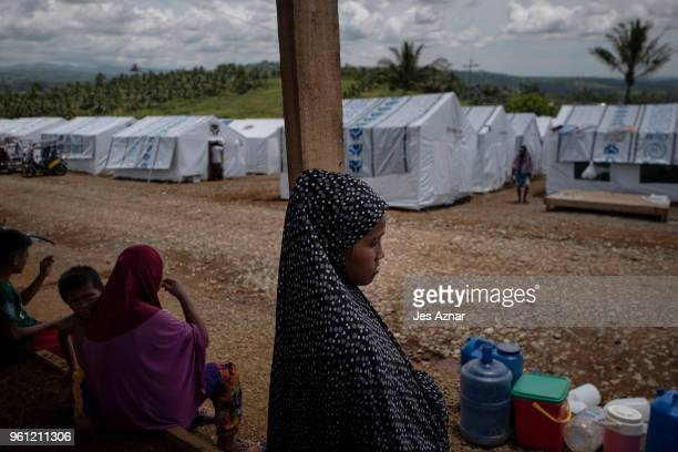 Displaced Marawi residents queue for water inside a makeshift tent shelter area on May 16 2018 in Marawi Philippines With their homes destroyed and...
