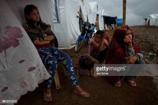 Displaced Marawi residents sitting in front of their shelter on the eve of Ramadan at the Sarimanok tent city on May 16 2018 in Marawi Philippines...