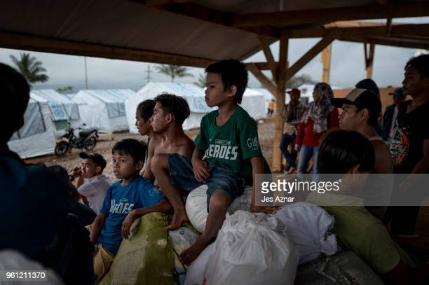 Displaced Marawi residents wait for food ration on the eve of Ramadan inside the Sarimanok tent city on May 16 2018 in Marawi Philippines With their...
